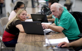 As the federal government pulls money out of the Affordable Care Act, its advocates and volunteers are helping to publicize the program and assist people with enrollments. (Raedle/GettyImages)