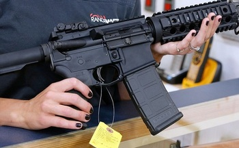 A customer examines an AR-15 semi-automatic rifle recently in a gun store. (Frey/GettyImages)