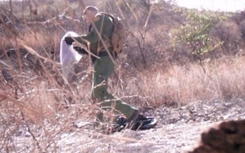 A video still from January 2017 shows a Border Patrol agent removing a blanket left for migrants. (No More Deaths)