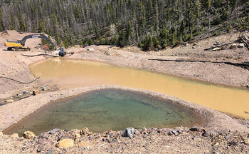 The defunct Mike Horse Mine must be perpetually treated so that it doesn't pollute the nearby Blackfoot River. (Earthworks/Flickr)