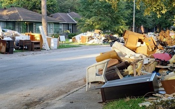 Flood damage debris lines a Houston residential street following Hurricane Harvey in 2017. More than 200,000 homes and businesses along the Texas Gulf Coast were damaged or destroyed by the storm. (IrinaK/AdobeStock)<br /><br />