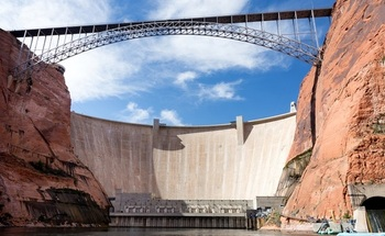 The Glen Canyon Dam towers 710 feet above the original Colorado River channel, producing hydroelectric power and impounding Lake Powell as a water storage reservoir. (Jason/Adobe Stock)