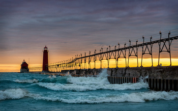 Grand Haven South Pier in Grand Haven, Mich. A new report says more intense storms and heavy flooding are putting Michigan residents and businesses at risk. (Adobe Stock)
