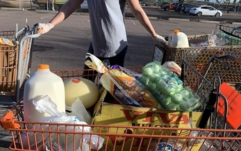 A volunteer helps distribute groceries last week at the Help Yourself Food Co-op, held every Friday in Mesa. It is sponsored by United Food Bank, part of the Arizona Food Bank Network and Feeding America. (United Food Bank photo)