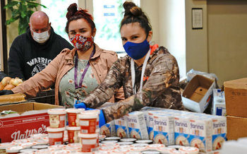 Yurok Health and Human Services staff members Courtney Mattz and Cassandra Charles assemble weekly food boxes. (Matt Mais/Yurok Tribe)