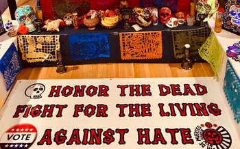 The public is invited to leave photos of their loved ones at a temporary altar built inside city hall in New Haven for Day of the Dead. (John Lugo)