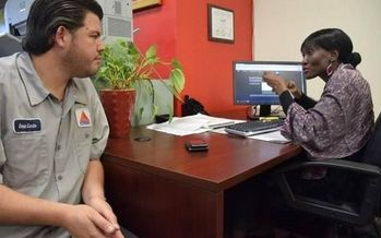 Navigator Natalie M. and consumer Omar Luna at Sant La Haitian Neighborhood Center review Luna's health-insurance options. (Epilepsy Florida)