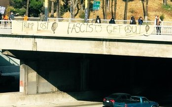 Anti-Trump protestors unfurled a banner over Interstate 110, a Los Angeles-area freeway, on Wednesday. (refusefascism.org)