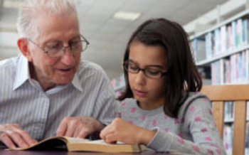PHOTO: Grandfather reading to child.