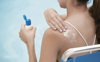 PHOTO: Woman putting on sunscreen.