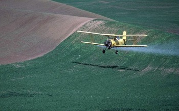 PHOTO: Aerial crop-spraying in northeast Washington. Photo credit: Ron Nichols, Natural Resources Conservation Service.
