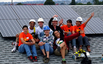 PHOTO: GRID Alternatives volunteers with a solar panel installed on a house in California. Courtesy GRID Alternatives.