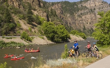 PHOTO: Bikers and rafters enjoy Glenwood Canyon, along the Colorado River. Courtesy Glenwood Springs Chamber Resort Association.