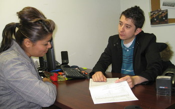 PHOTO: Utah's Community Health Centers are already accustomed to doing outreach work with patients. Here, AmeriCorps worker Erik Perez explains a CHIP application to a local mom. Courtesy AUCH.
