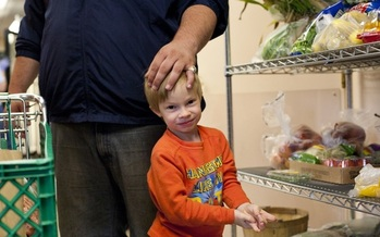 PHOTO: SNAP recipients will see food aid reduced this fall when a boost in benefits from the ARRA expires. Additional cuts proposed through the Farm Bill could further reduce benefits. Photo: boy at a food pantry. Credit: Jessie Gladin-Kramer.