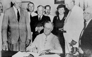 President Franklin D. Roosevelt, signing the original Social Security Act on August 14, 1935, calls it,