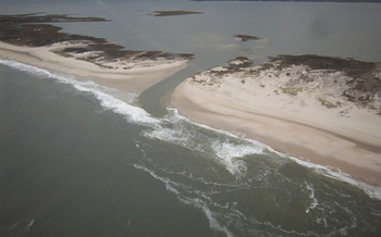 """PHOTO: One year ago, Superstorm Sandy cut a breach through a narrow part of Fire Island. In one of the hurricane's few """"silver linings,"""" that cut resulted in slightly less damaging brown tide this summer in Great South Bay. Courtesy National Parks Service."""