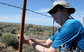 PHOTO: Richard Brandt, Portland, secures a new wire on a boundary fence at Hart Mountain National Antelope Refuge in southern Oregon. Replacing the bottom line of barbed wire with smooth wire makes the fencing safer for the antelope that migrate through the area. Photo courtesy Oregon Natural Desert Assn.